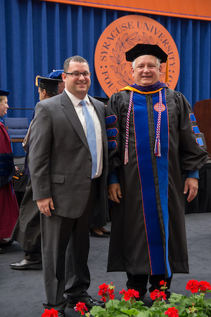 Brian Bauersfeld L'04 (left) hooded his father Nelson L'14 at his Commencement ceremony.