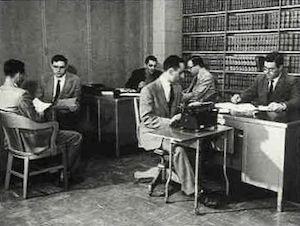 Surrounded by library volumes, members of the Syracuse Law Review staff gather, possibly in the 1950s.