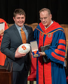 Thane Green accepts the Chancellor's Medal on behalf of his father, Tim Green L'85